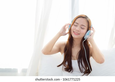 Beautiful asian young woman enjoy listen music with headphone while sitting in bedroom, relax girl with earphone internet online, leisure and technology concept.