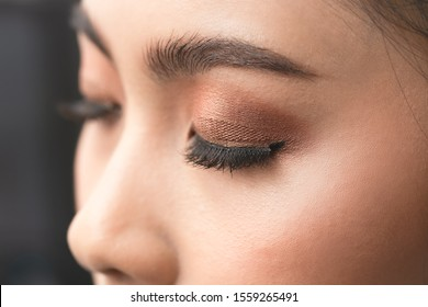 Beautiful asian young woman with eyelash extensions applying mascara.