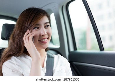 Beautiful asian young woman making phone call in car as passenger