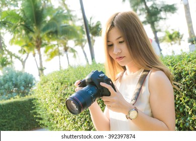 Beautiful asian young woman photographer taking outdoor portraits