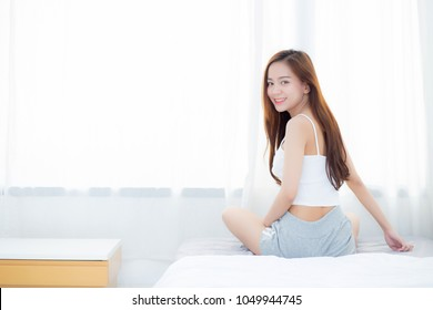Beautiful asian young woman smiling with happiness leisure sitting on bed at home by the window, girl relax and wellness concept.