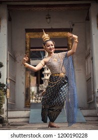 beautiful asian young woman in thai traditional dress dancing traditional thai dance in Thai buddhist temple in bangkok wat suthat. outdoor next to temple
