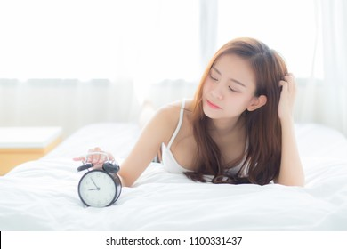 Beautiful asian young woman turn off alarm clock in morning, wake up for sleep with alarm clock, relax and lifestyle concept.