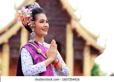 Beautiful asian young woman wearing thai traditional dress are raising hands to pay respect in  buddhist temple  which is a symbol of Thailand. The costume of the national dress of ancient Thailand.