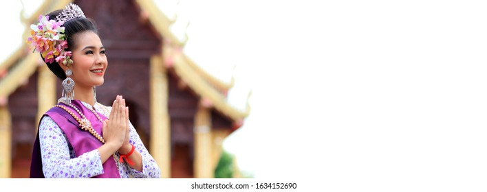Beautiful asian young woman wearing thai traditional dress are raising hands to pay respect in  buddhist temple which is a symbol of Thailand. The costume of the national dress of Thailand. Copy space