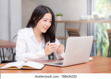 Beautiful asian young woman working online on laptop sitting at coffee shop, professional female freelancer using notebook computer with connect to internet for distance job.