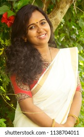 Beautiful Asian/Indian/Kerala girl/woman in traditional saree and kalamkari blouse standing outdoor during Onam celebrations