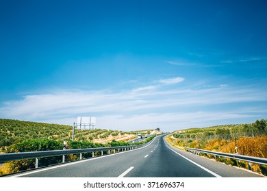 Beautiful asphalt freeway, motorway, highway against the background of southern Spanish landscape. Travel road concept. Andalusia, Spain.