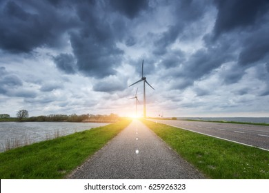 Beautiful asphalt road with wind turbines generating electricity at sunset. Windmills for electric power production. Landscape with road, green grass and wind mills and blue cloudy sky in spring