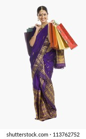 Beautiful Assamese woman holding shopping bags and smiling