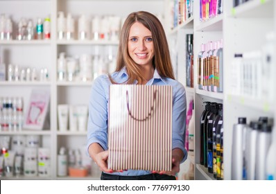 Beautiful assistant saleswoman with paper bag at beauty store, cosmetic shopping