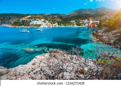 Beautiful Assos village, Kefalonia. Greece. White cruise yachts staying at anchor in beautiful emerald green colored lagoon water. Dry pine trees branches in foreground