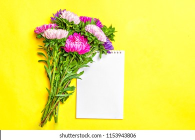 Beautiful Aster Flowers, white notepad on pastel pink color background mock up with copy space for your text. Flat lay, top view Concept of spring, summer and autumn