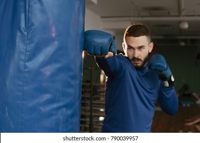 A beautiful athlete boxer punches a boxing pear. Kickboxer trains before the fight. Kickboxing for man. Sexy strong  fighter. Kickboxing man training punching bag