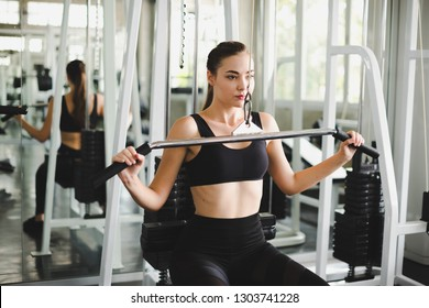 Beautiful athlete exercising with a lat pulldown machine to play the arms and shoulder muscles in the gym. Exercise in the gym concept.