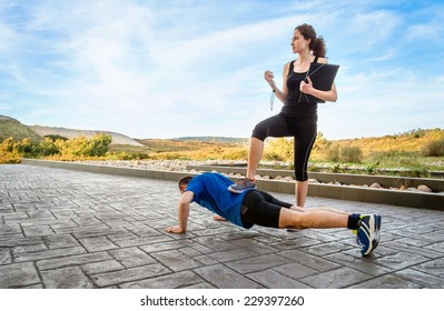Beautiful athlete girl coach training very hard a man while timing the push ups with chronometer
