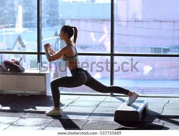 フィットネスクラブで運動する美しい運動選手の女性。