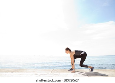 Beautiful athlete woman preparing to run against a blue sky and sea space, healthy lifestyle. Wellness and well being, training sport, active female care and fitness. Graphic body shape figure.