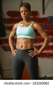 Beautiful, athletic African-American woman in work out clothing posing in urban gym.