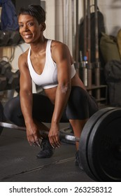 Beautiful athletic African-American woman working out with free weights in urban gym.