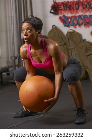 Beautiful athletic African-American woman working out with weighted medicine ball in urban gym.