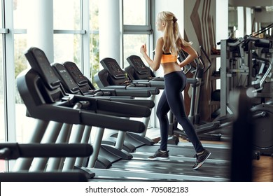 Beautiful athletic blond woman running on a treadmill at the gym.