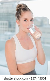 Beautiful athletic blonde in bright room drinking water