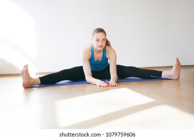 Beautiful athletic blonde girl doing sports exercises on a sports mat.