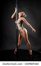 Beautiful athletic busty elegant blonde girl performs artistic elements of an exotic dance on a gray background. Health, lifestyle, sports design. Copy space