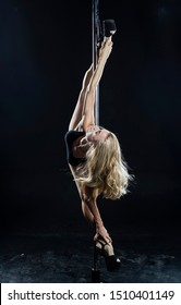 Beautiful athletic busty elegant blonde girl performs artistic elements of an exotic dance on a black background. Health, lifestyle, sports design. Copy space
