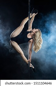 Beautiful athletic busty elegant blonde girl performs artistic elements of an exotic dance in a theatrical smoke. Health, lifestyle, sports design. Copy space