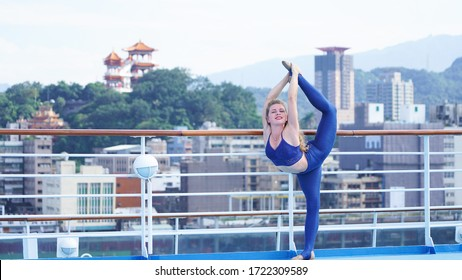 Beautiful athletic curly girl in bright clothes on deck of cruise ship performs gymnastic split. Flexible blonde acrobat smiles while standing in split against background of an Asian city, temple.
