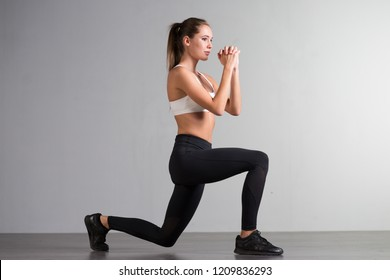 Beautiful athletic fitness young woman doing sports exercises on a gray background