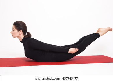 Beautiful athletic girl in a black suit doing yoga. viparita naukasana asana boat pose. Isolated on white background.