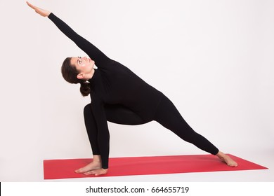 Beautiful athletic girl in black suit doing yoga asanas. Isolated on white background