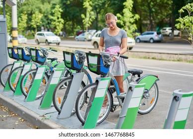 Beautiful athletic girl blonde in a skirt rent a bike in Almaty