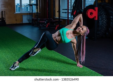Beautiful athletic girl in colored sportswear posing in the gym. Young beautiful fitness model with African braids in the gym engaged in Pilates