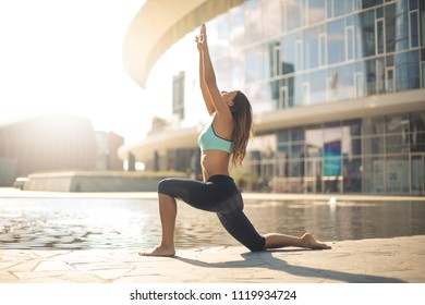 Beautiful athletic girl doing yoga positions in the street