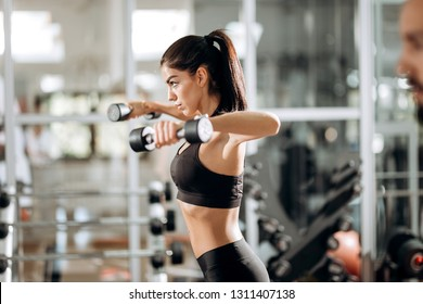 Beautiful athletic girl dressed in black sports top and tights builds up muscles with dumbbells in the gym