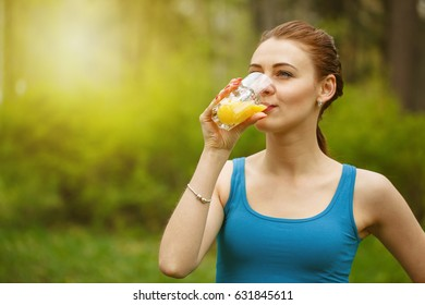 Beautiful athletic girl drinks juice from a glass beaker after training on the street, city sports