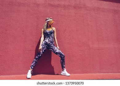 Beautiful athletic girl in a jumpsuit on the playground. Fashion