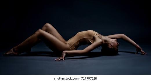 Beautiful athletic girl on the floor. Studio portrait in motion