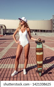 Beautiful athletic girl posing board longboard skateboard, summer city lifestyle, fashion modern trend. Tanned figure, fitness. The concept weekend holiday. Sunglasses baseball cap, white swimsuit.