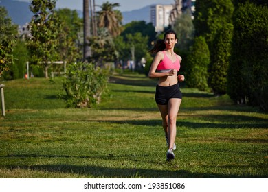 Beautiful athletic girl running in the green park, bright sportswear