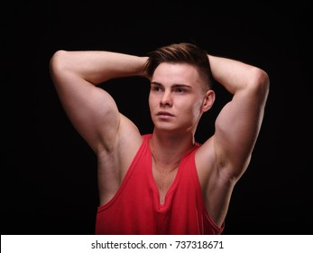 Beautiful, athletic guy with sexy muscles on a black background. Youth confidence concept.