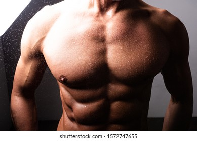 Beautiful, athletic, male torso. In contrast lighting. With shine and water.