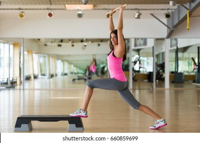 Beautiful athletic woman doing stretching exercise in gym with bar.
