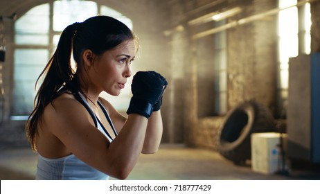 Beautiful Athletic Woman holds her Arms Ready for Defending Herself. It is a Part of Her Intensive Fitness Gym Training.