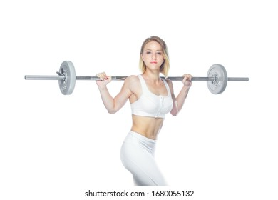 Beautiful athletic woman pumping up muscles with barbell on white background
