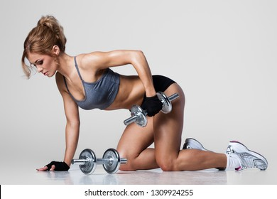 Beautiful athletic woman pumping up muscules with dumbbells on gray background